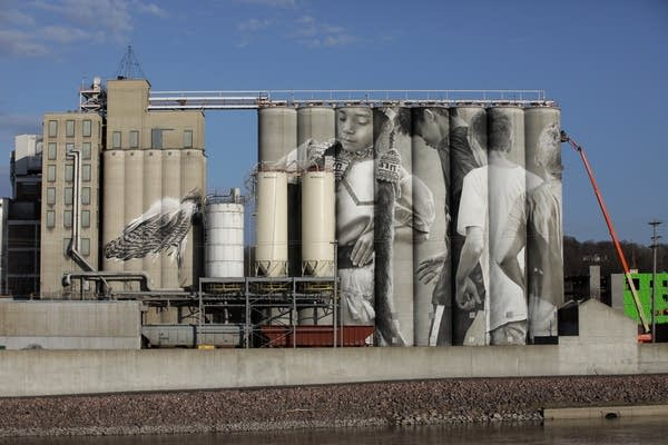 large silos painted with images of young children dancing