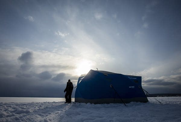 Hannah Hudson emerges from her ice fishing shelter.