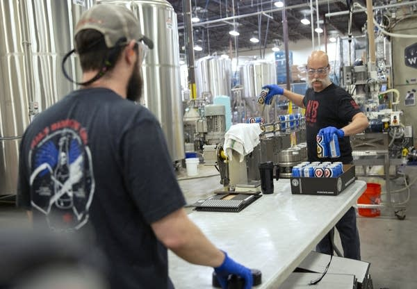 Jeff North and Collin Russell pack cans of Pahlay, a hazy pale ale.