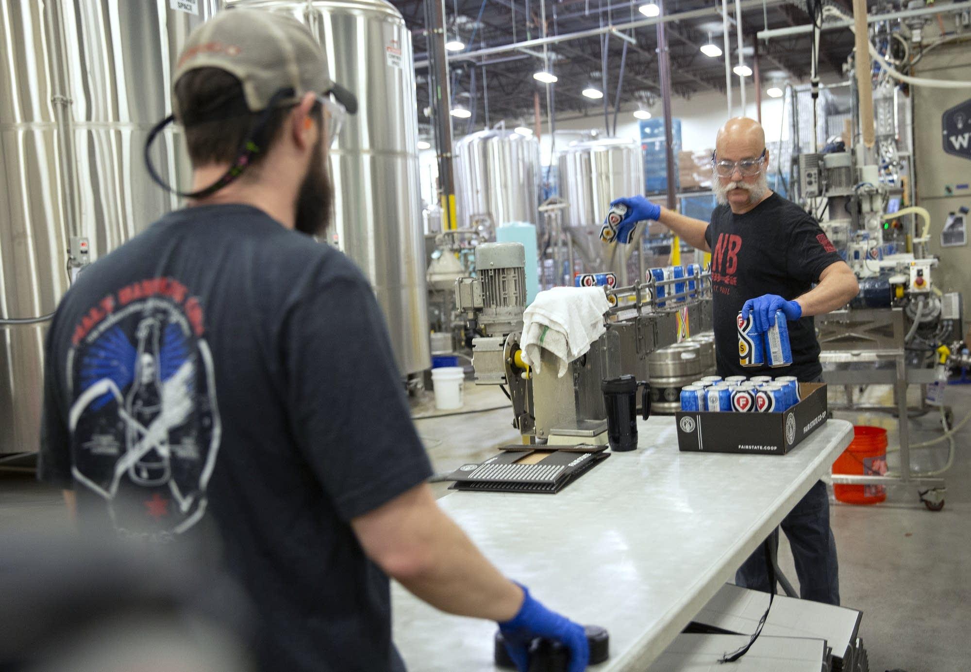 Jeff North et Collin Russell emballent des canettes de Pahlay, une bière blonde pâle.