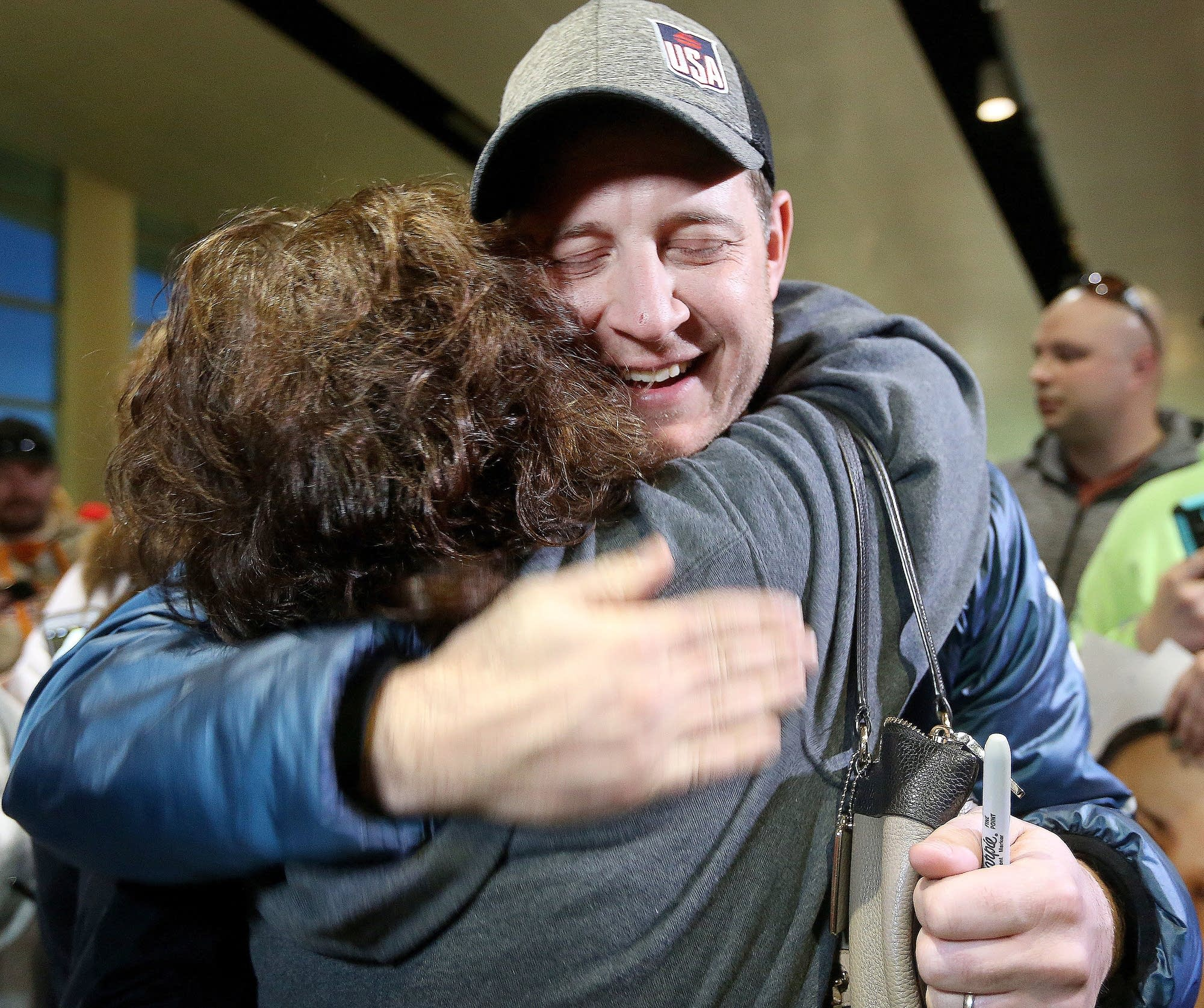 John Shuster of the Duluth curling team gets a big hug from Kim Hinz.
