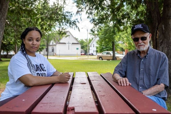 Two people sit across from each other at a picnic table.