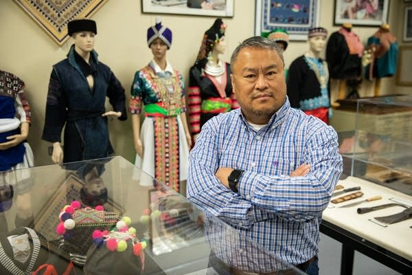 A man with his arms crossed stands in a room of Hmong artifacts.
