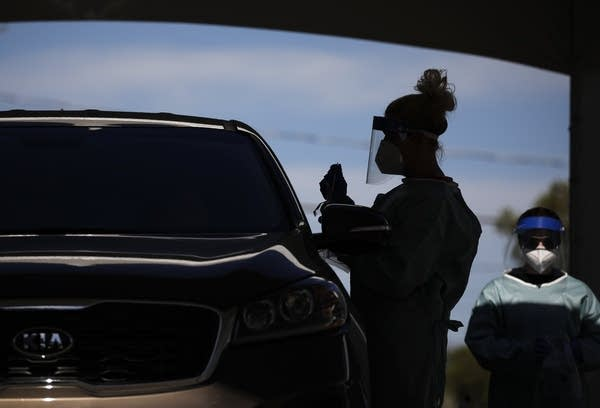 Health care workers test patients at a drive-thru COVID-19 testing site.