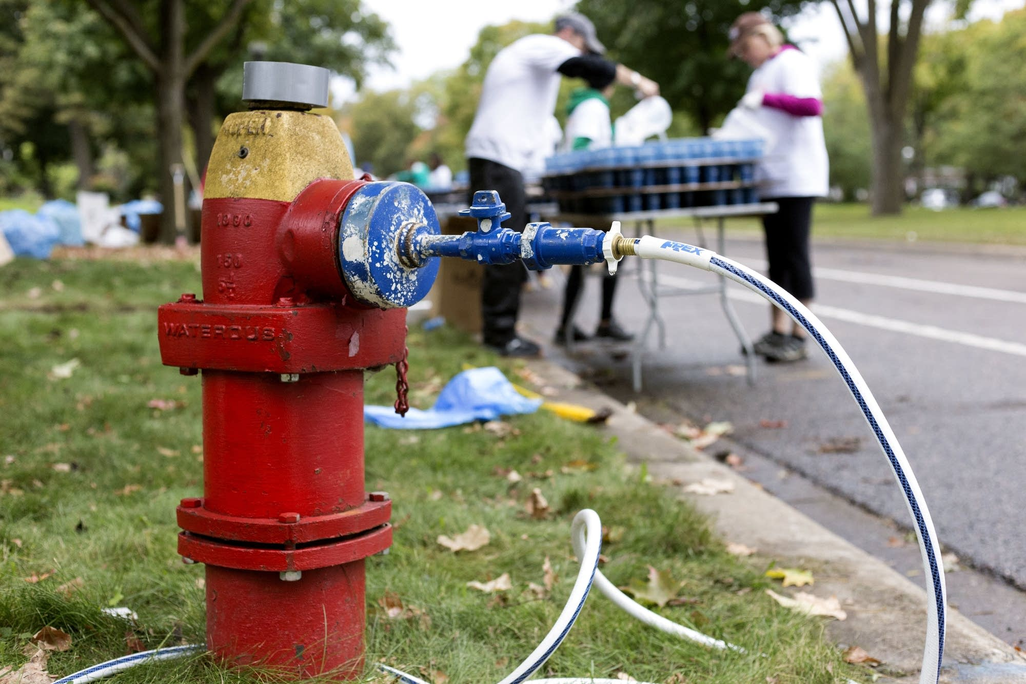 Volunteers filled water cups for marathon participants from fire hydrants.