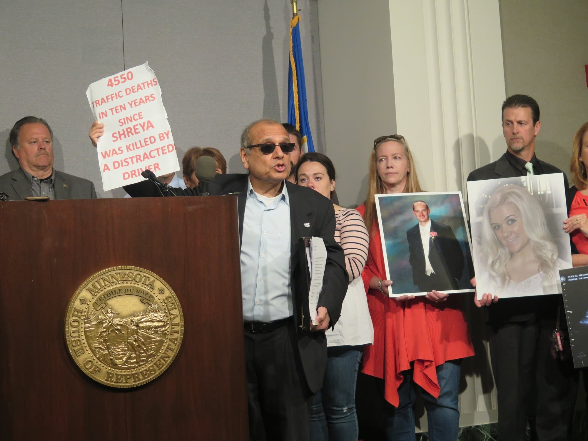 Vijay Dixit holds up a sign about distracted driving deaths.
