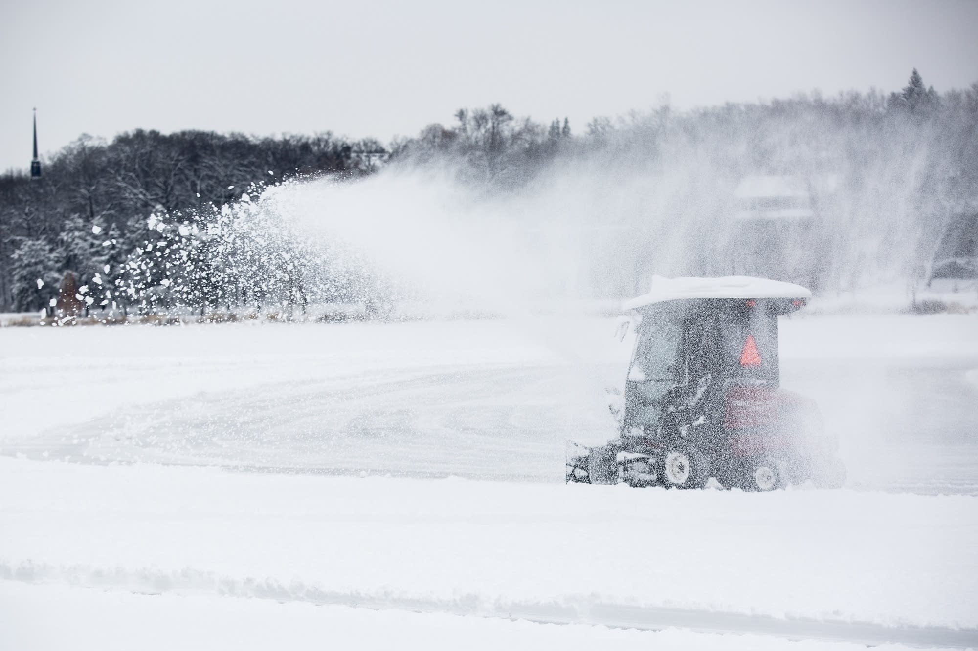 A snowblower sprays snow as it clears ice on Lake of the Isles