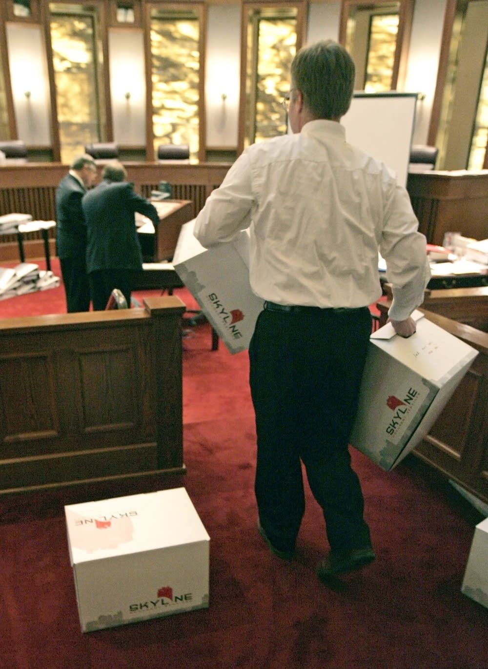 A court employee brings in boxes of exhibits