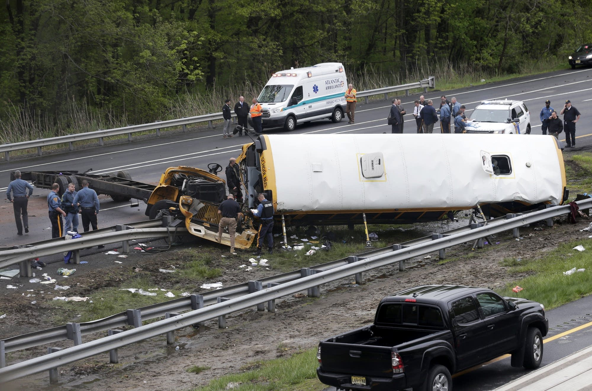 Emergency personnel work at the scene of a school bus, dump truck collision