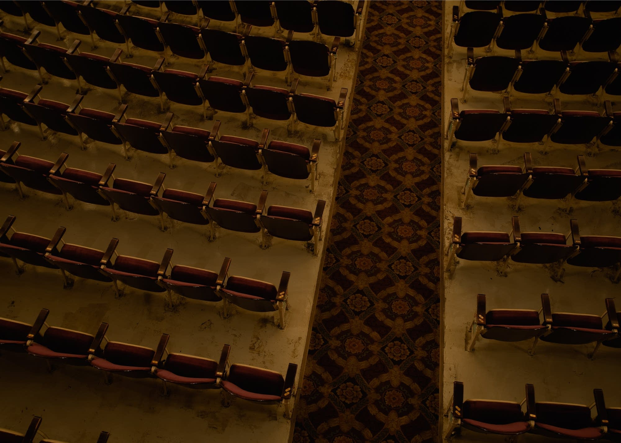 Rows of empty red chairs are bisected by a patterned, lush carpet.
