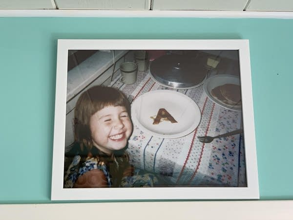 An old photo of Luke's daughter with a pancake in the shape of an A