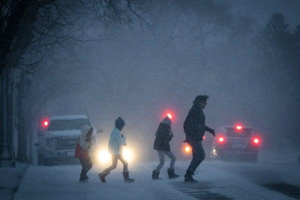 People dash across the street during a snowstorm.