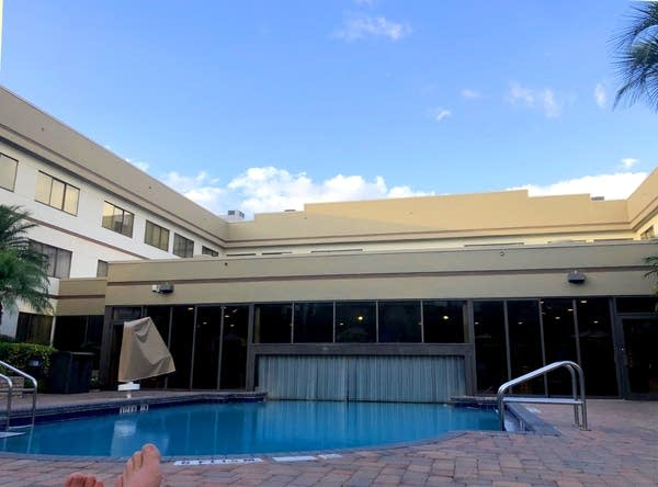 Photo of a hotel pool that is both indoor/outdoor split by plastic hangings