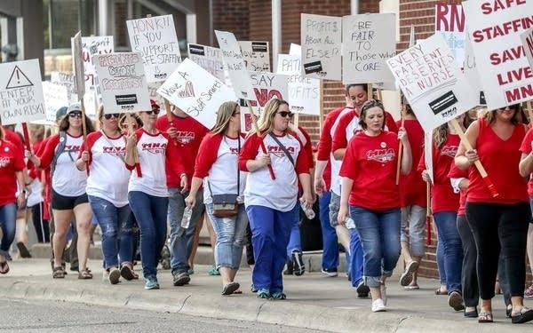 Marchers walk along a picket line