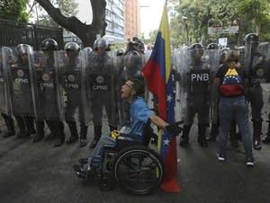 A demonstrator yells at members of the Venezuelan National Police