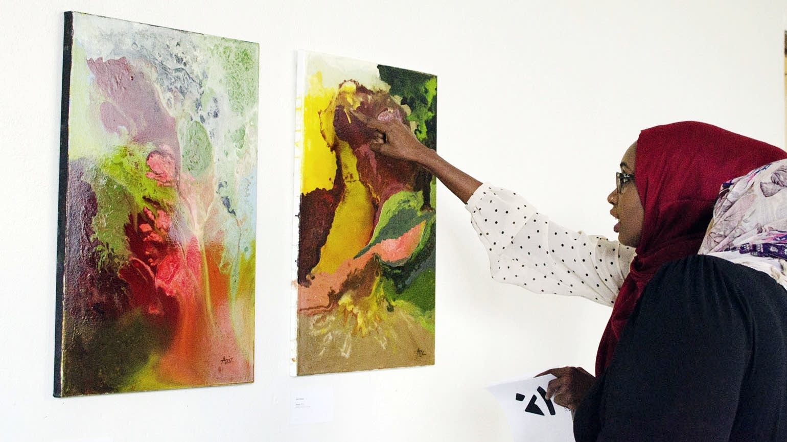 Jihan Ali and a friend examine abstract paintings.