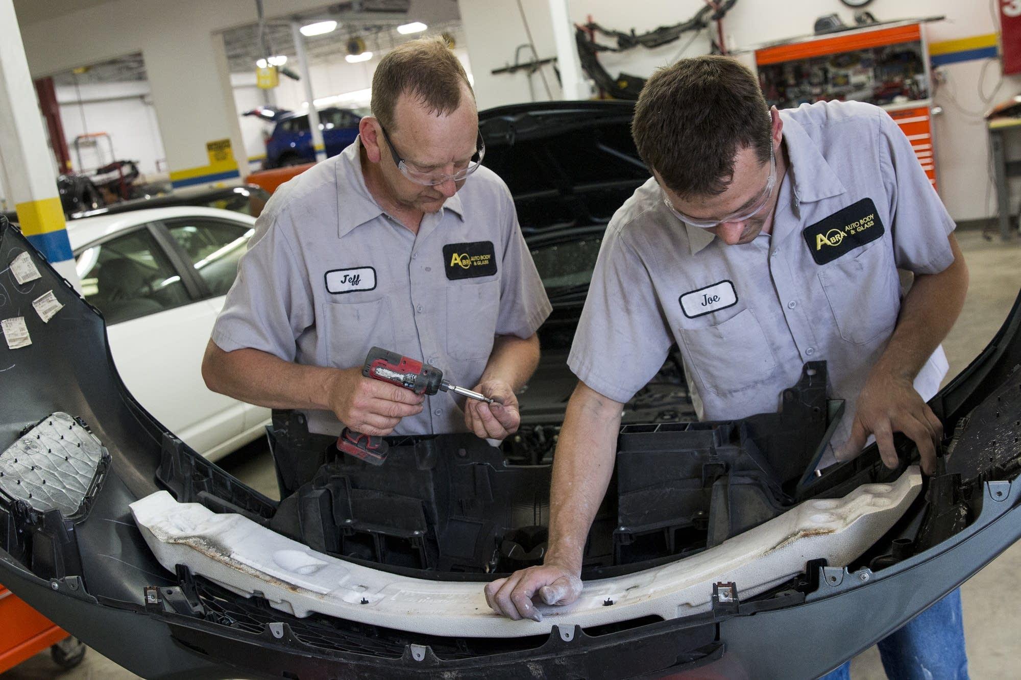 Abra employees install a bumper.