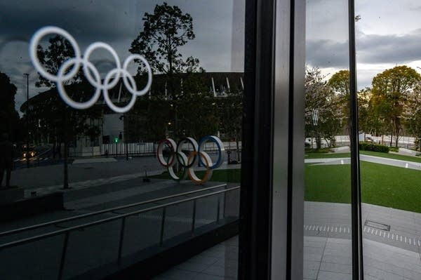 The Olympic rings are seen reflected in a window.
