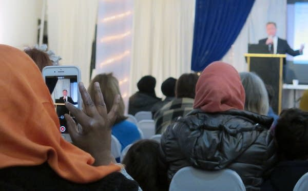 A Somali-American woman records video with her phone