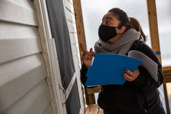 A woman holding a blue folder speaks through a screen door.