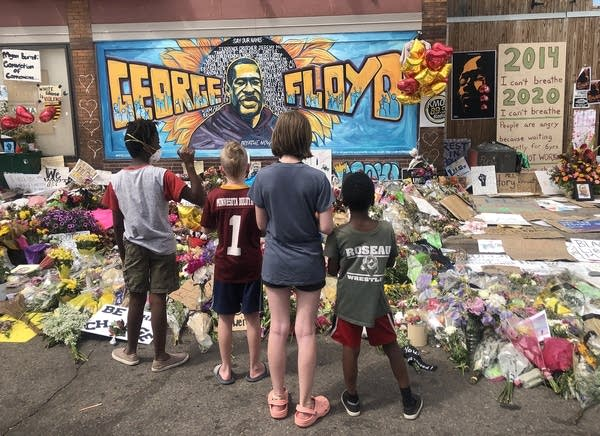 A family looks at a mural at a memorial.
