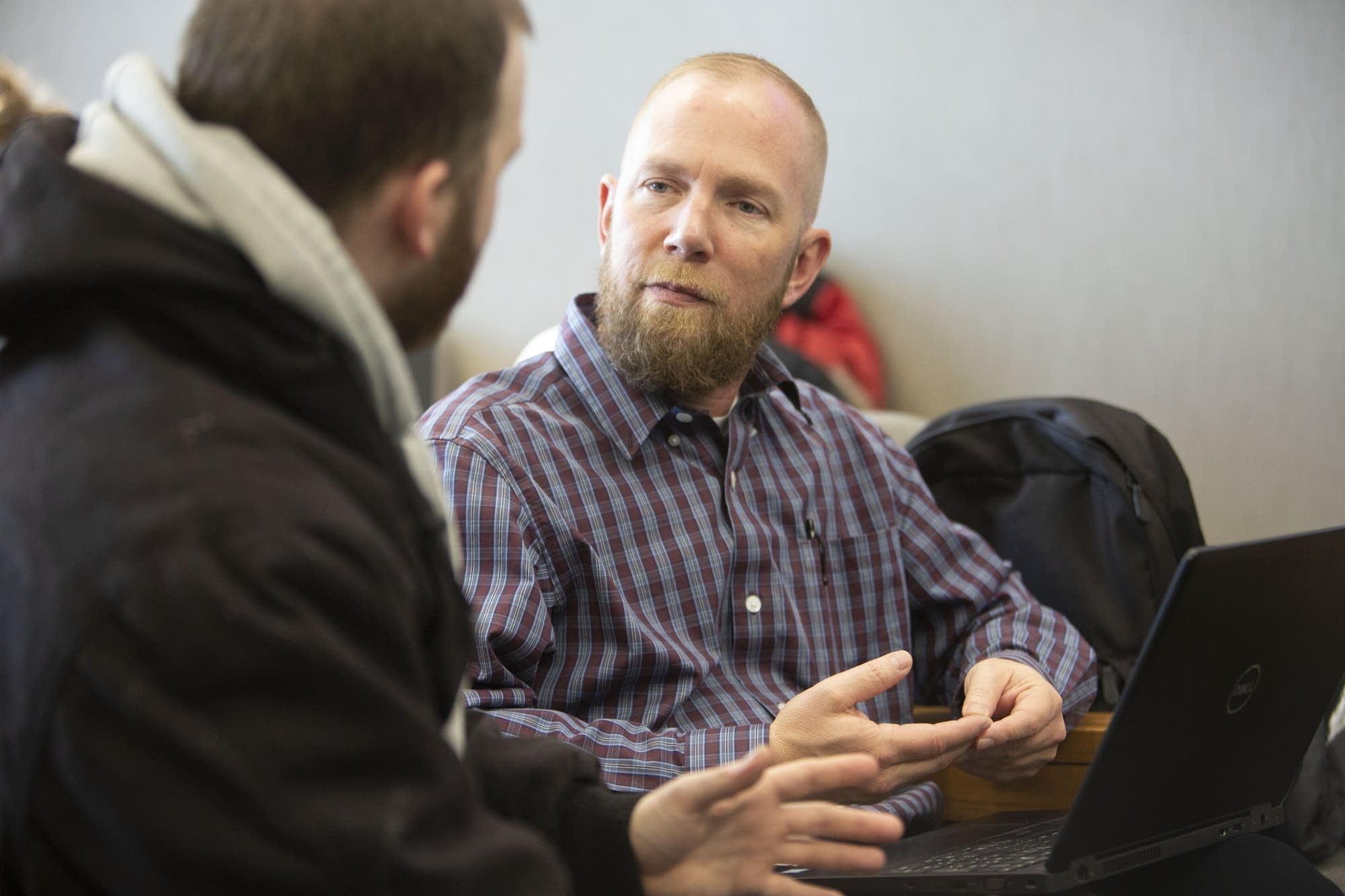 Certified financial counselor Chad Larimer (right) talks with Josh Stone.
