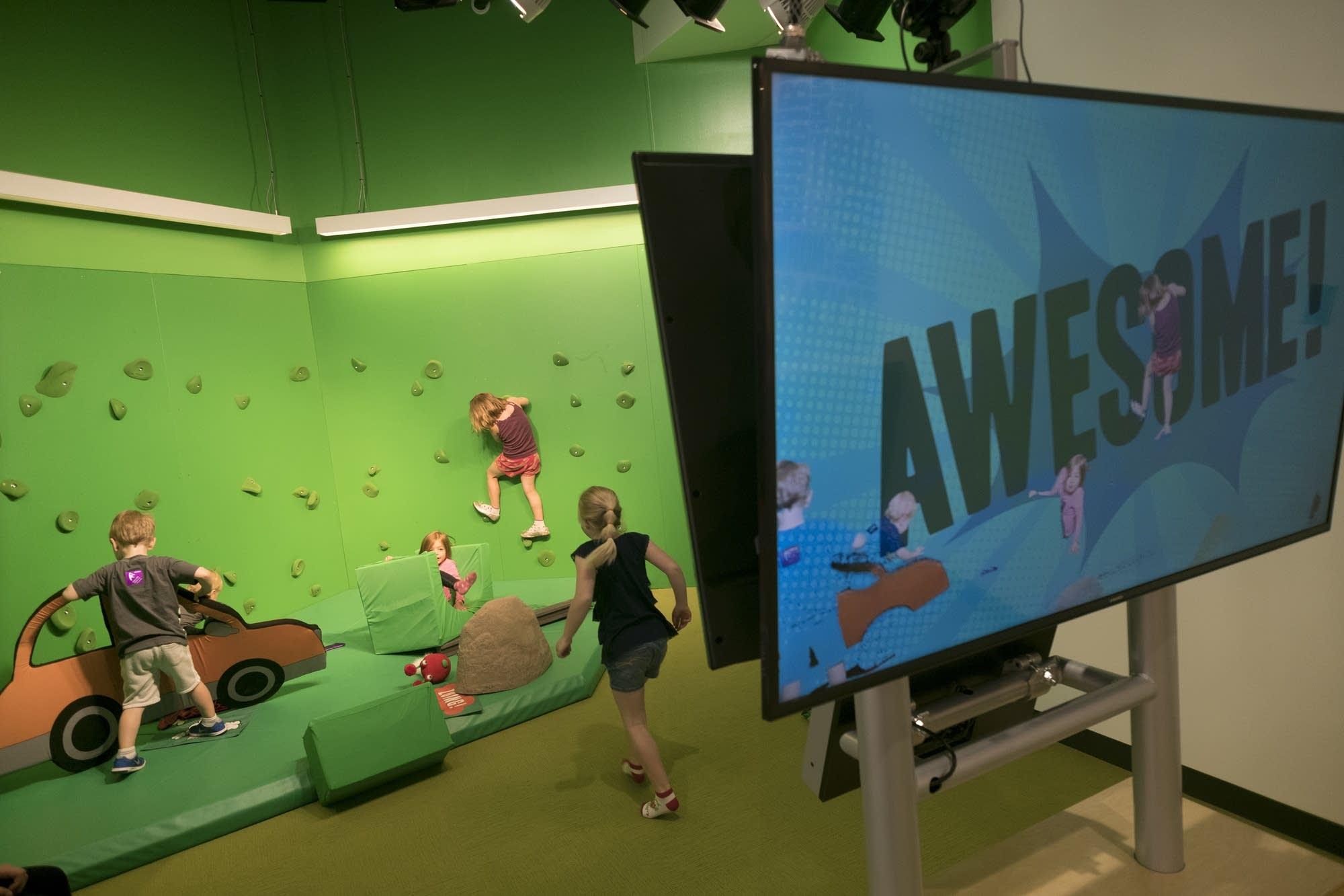 Kids climb on a green screen.