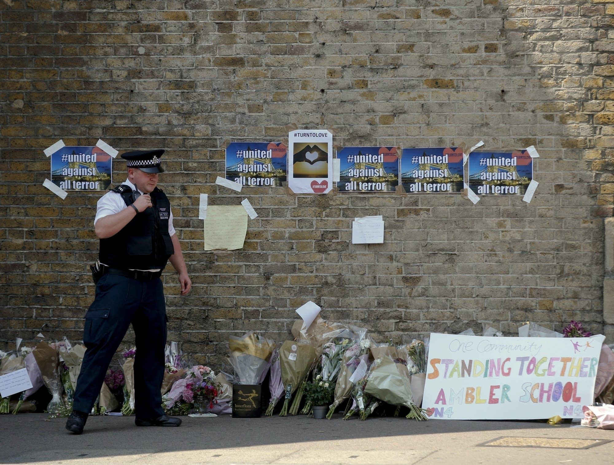 A policeman stands near floral tributes