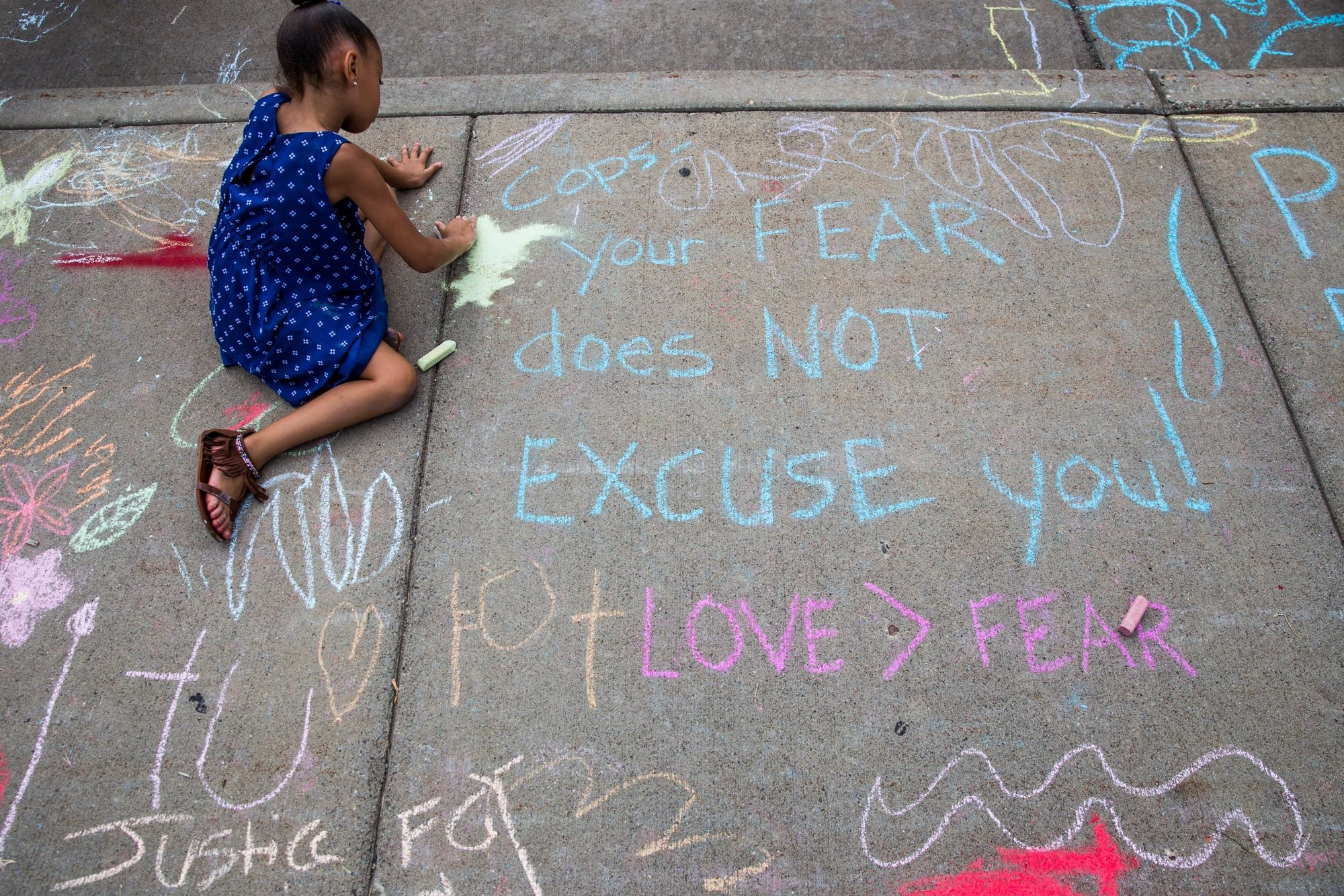 A young protester draws with chalk.
