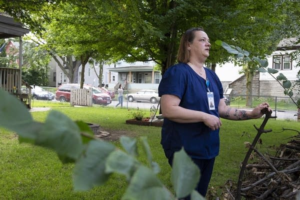 A woman wearing scrubs stands in the front yard of a house.