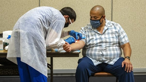 A man sits in a chair as another person prepares to take a blood sample.