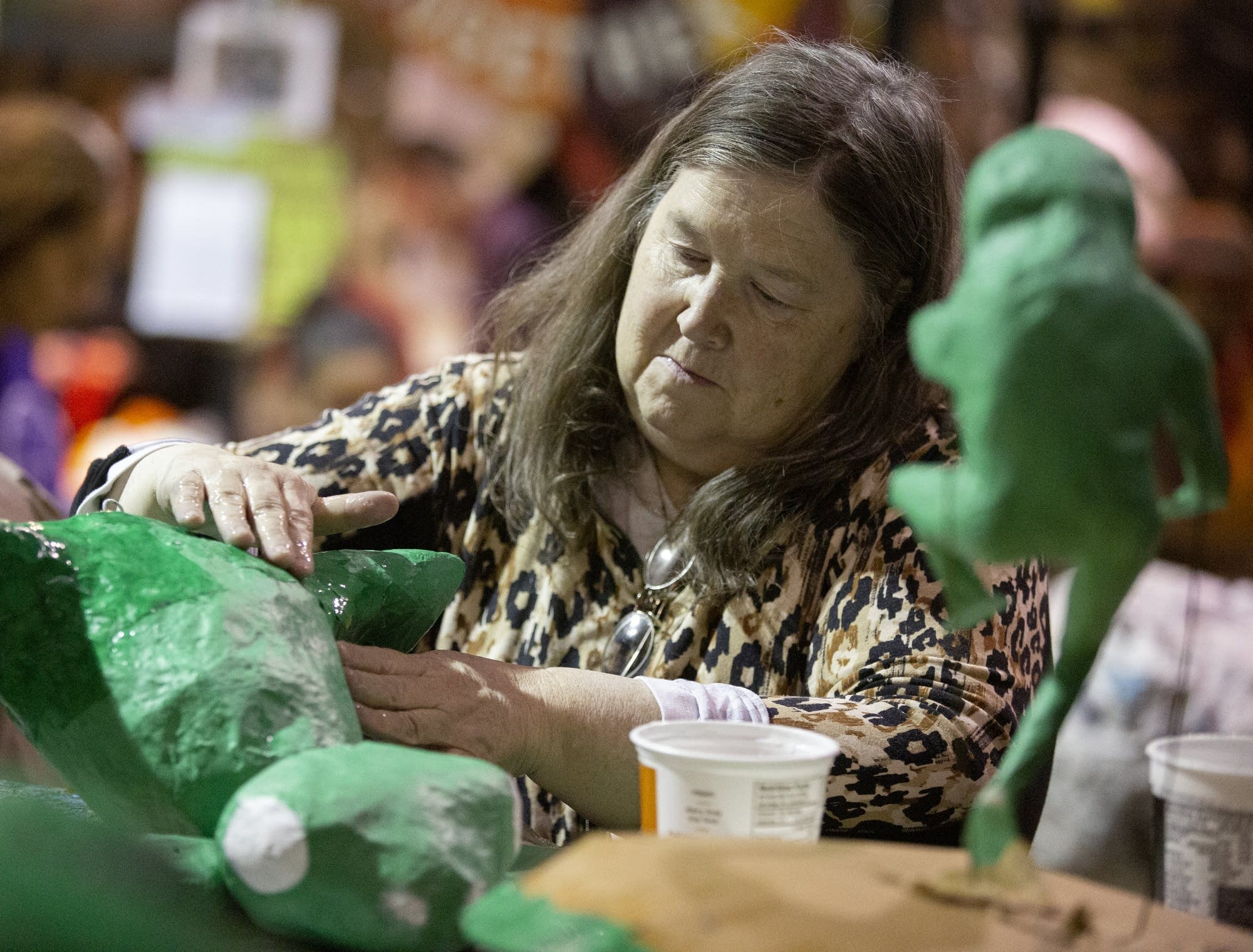 Nell Nere of St. Paul patches up a paper mache frog puppet.