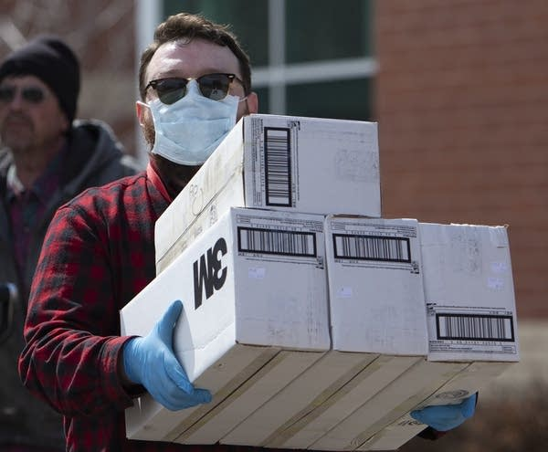 A man wearing a mask carries boxes.