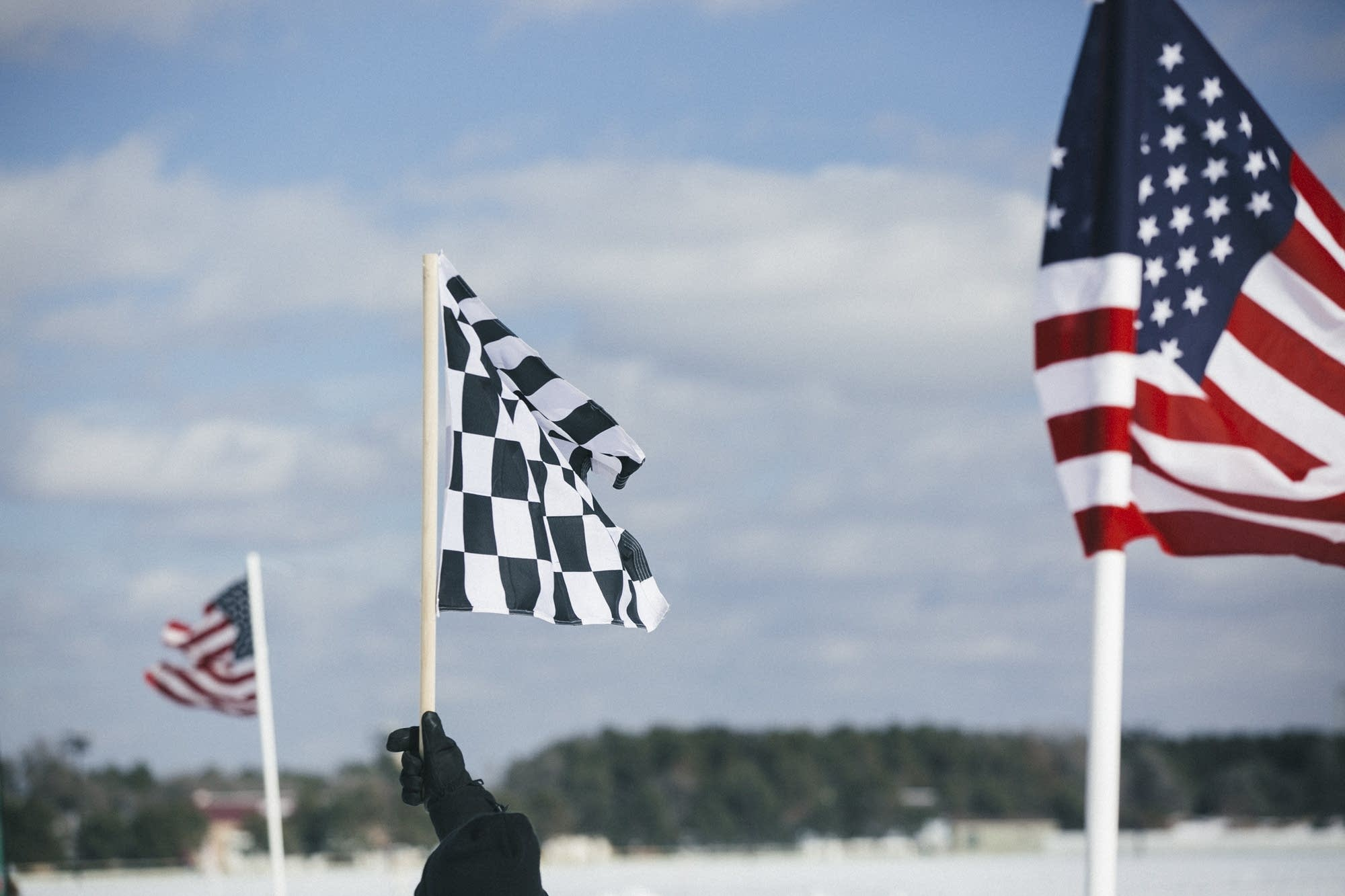 A checkered flag flies at the end of the skijoring track.