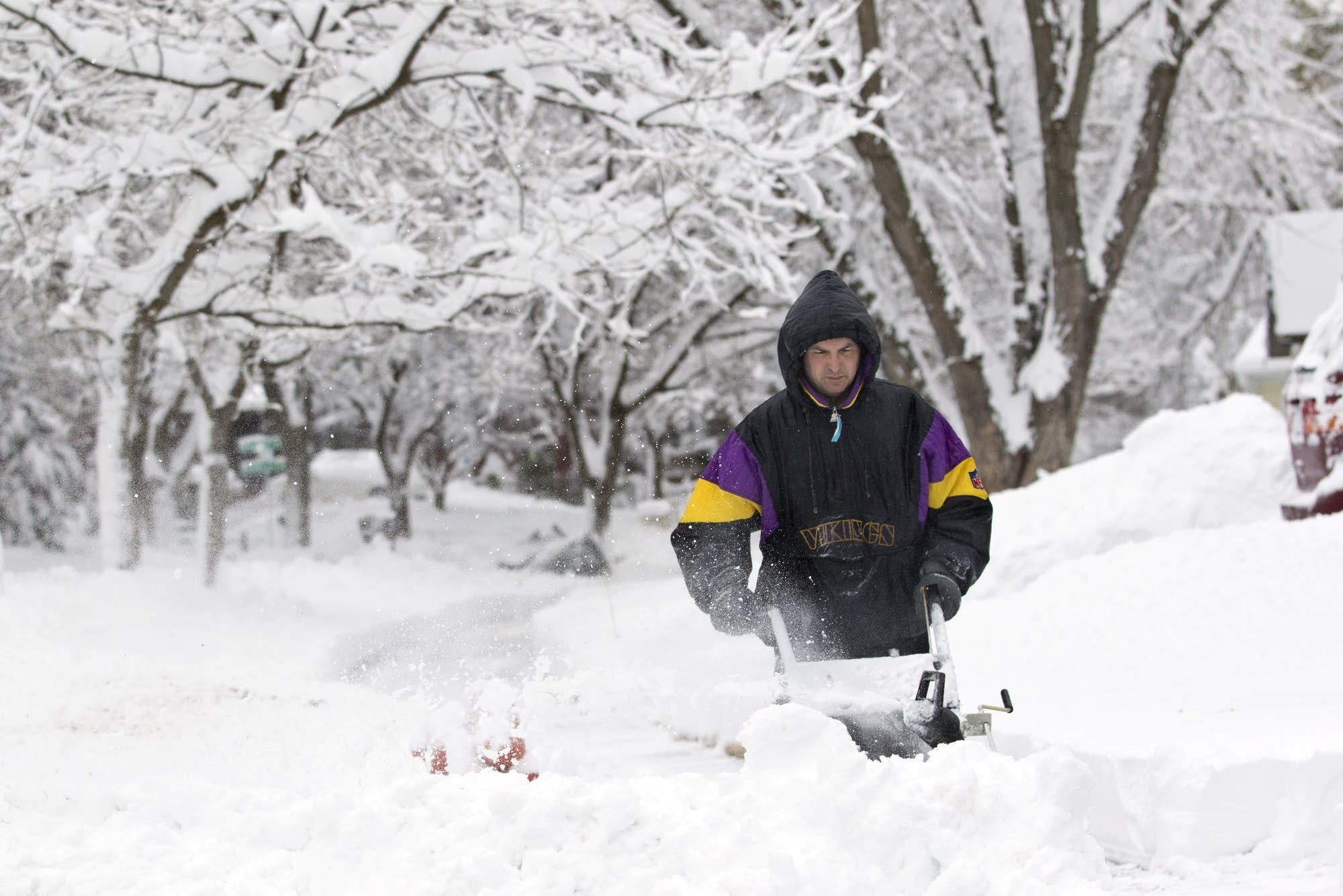 Ric Dwyer, of Rochester, works to clear his drive and sidewalk.