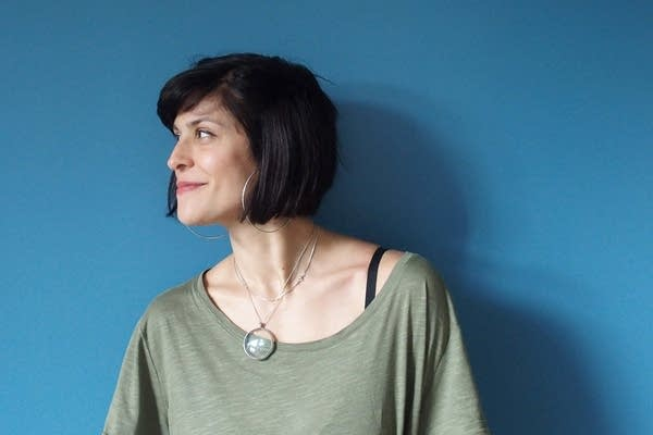A woman with short dark hair wearing a green shirt in front of a blue wall