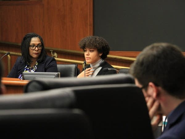 A woman testifies at a hearing about her experience.