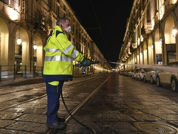 An operator sanitizes the streets in Turin, Italy
