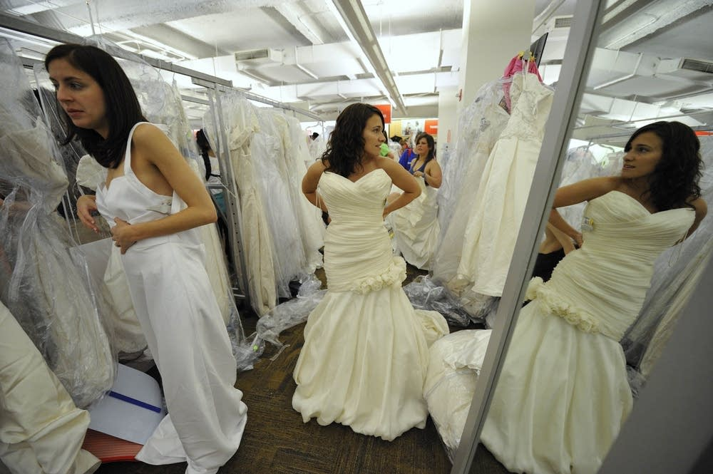 Women try on wedding dresses