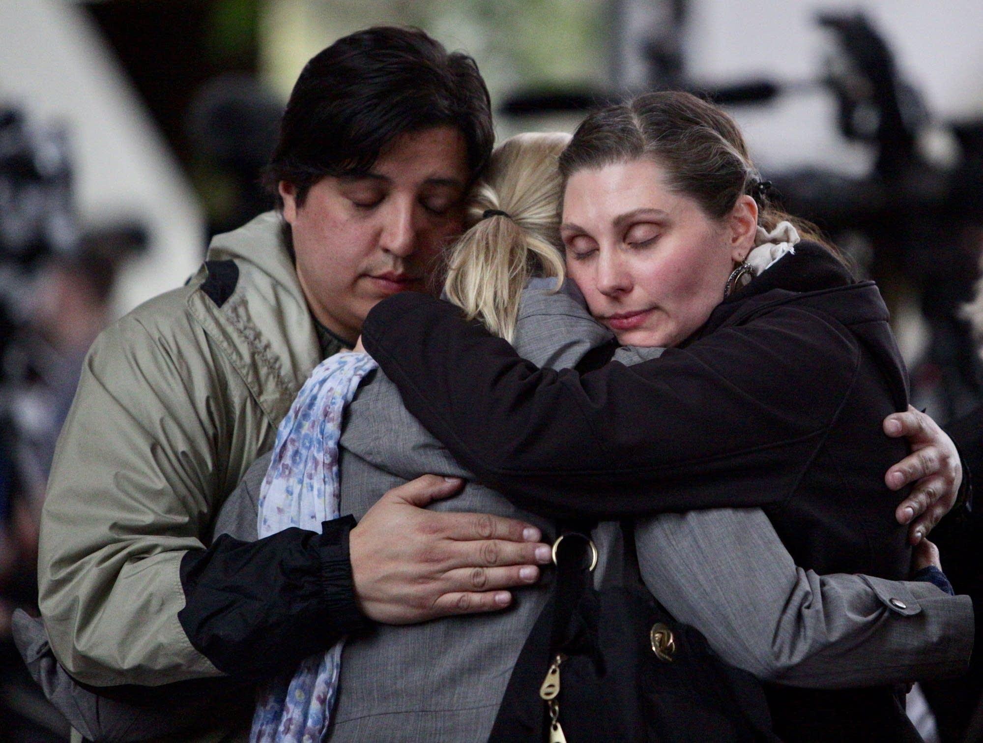 Crowd members hug after a verdict in the Noor trial