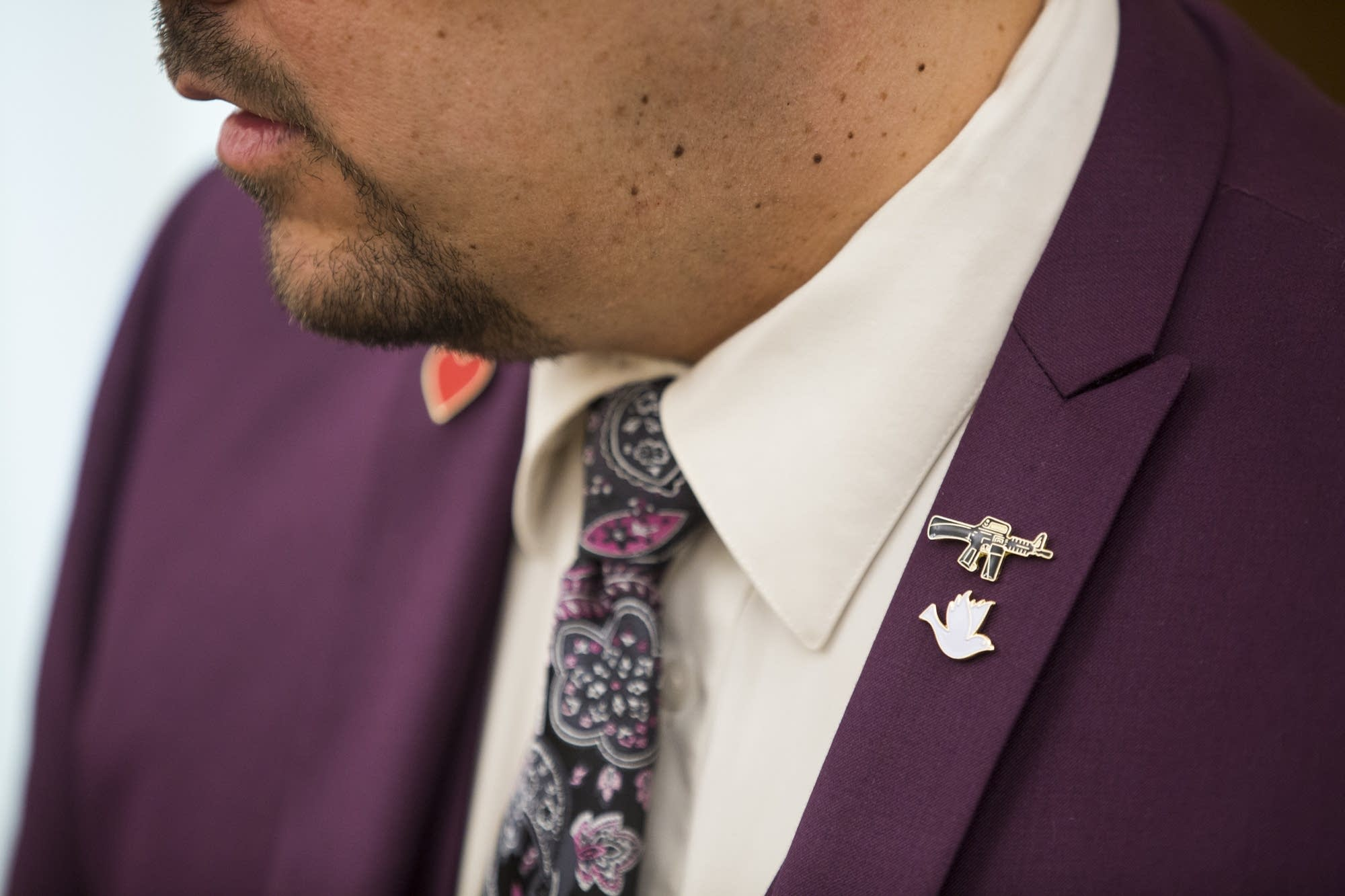Eric Lucero wears pins in the shape of a dove, heart, and an assault rifle