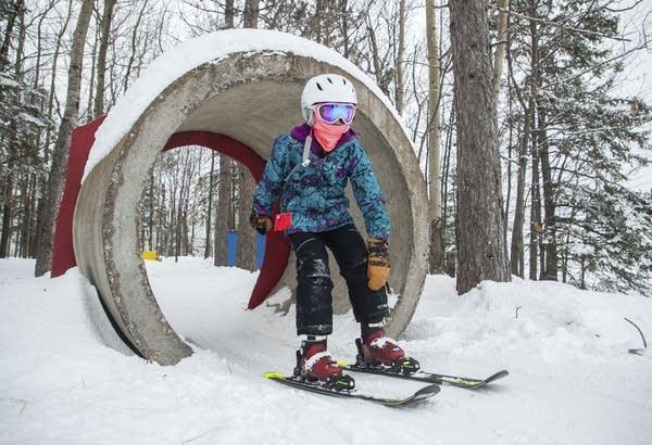 A child skis through a concrete tube on a ski slope.