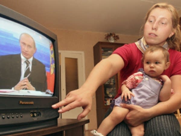An infant watches TV
