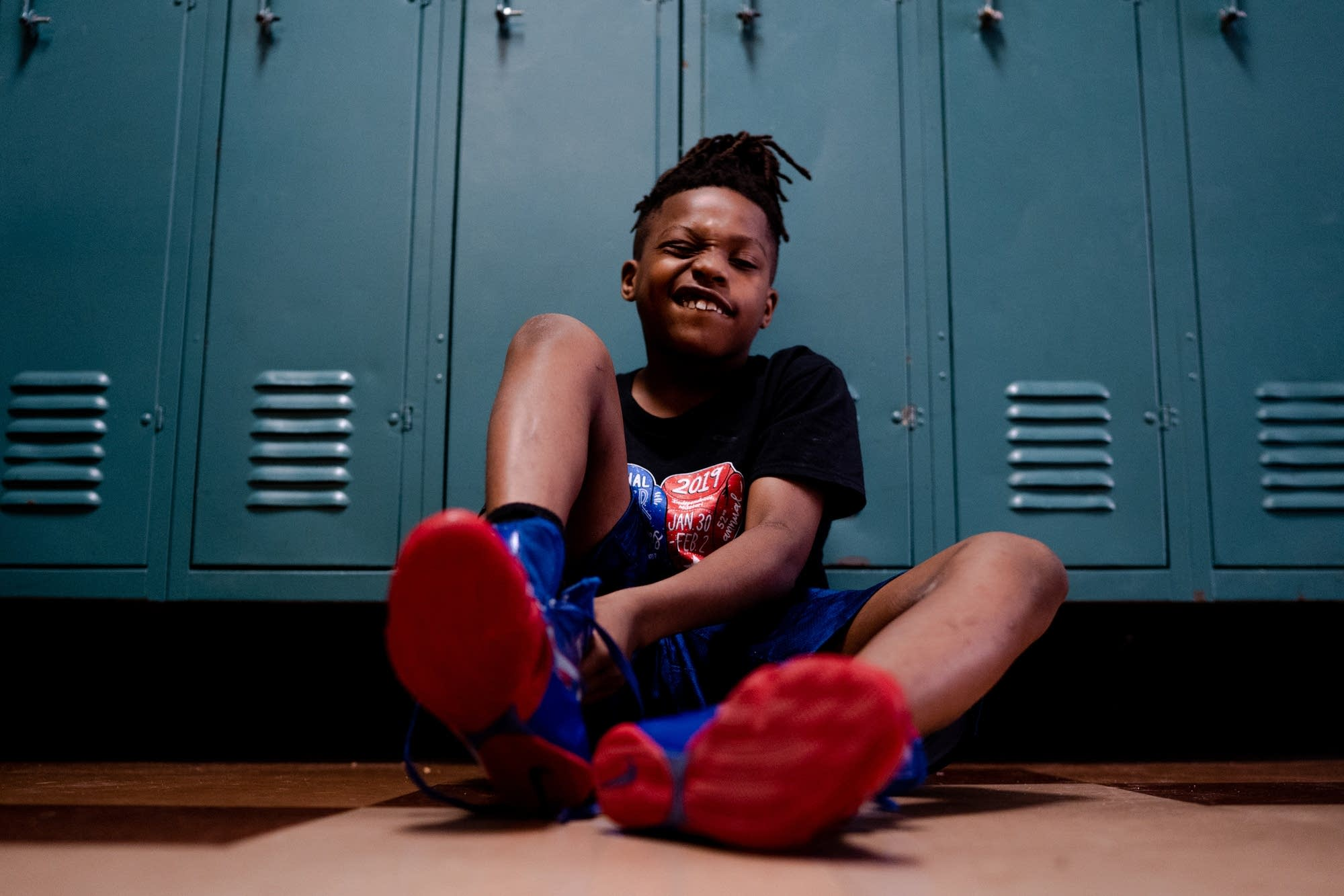 Eleven-year-old Morgan McDonald Jr. pulls on his boxing shoes.