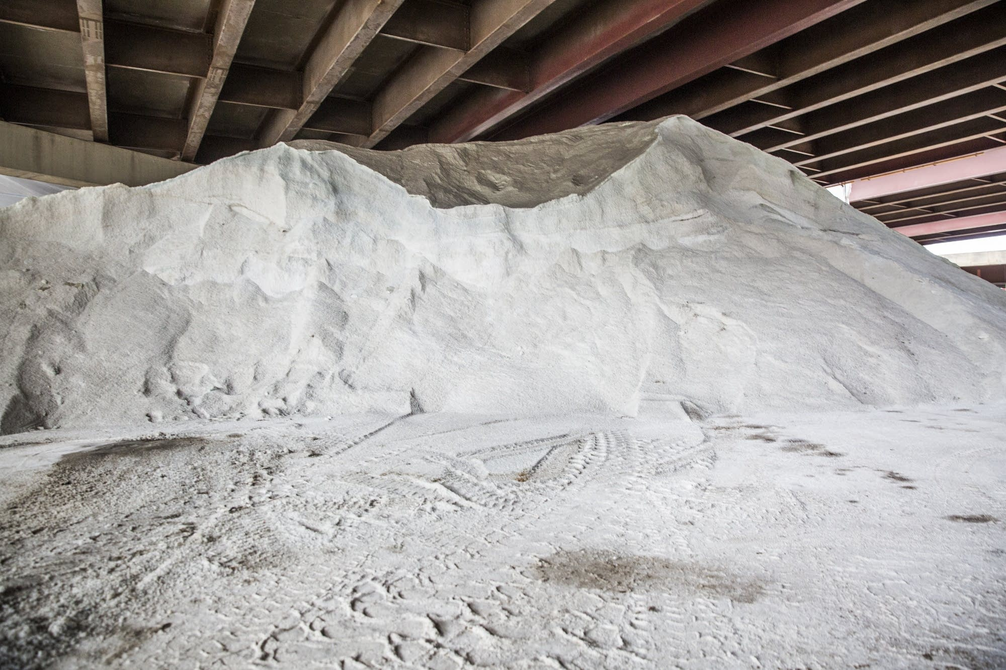 A pile of road salt sits underneath an overpass.