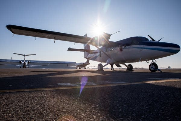 The sun shines over a plane sitting on an airfield