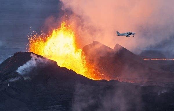 A plane flies near the volcano