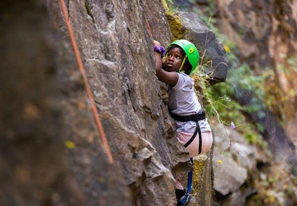 A young girl goes rock climbing.
