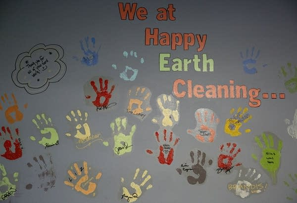 "Handprints are painted a wall with the words ""We at Happy Earth Cleaning"""