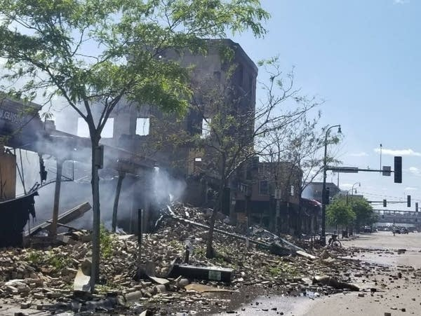 Smoke and rubble can be seen from a city street.